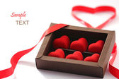 Red valentines small hearts in brown paper box — Photo