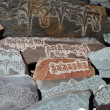 Detail of written mantra on buddhist mani stones - Stock Photo