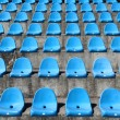 Old plastic blue seats on football stadium — Stock Photo