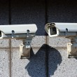 Royalty-Free Stock Photo: Two white security cameras on the concrete wall