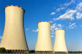 Three cooling towers on the green field — Stock Photo