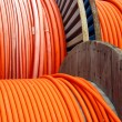 Stock Photo: Orange wire on wooden spools