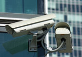Two surveillance cameras and glass — Stock Photo