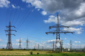 Electricity pylons in the green field — Stock Photo