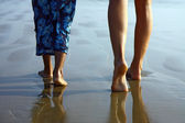 Detail of child and girl legs walking on the beach — Stock Photo