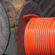 Wooden spools with black and orange cables — Stock Photo