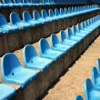 Blue plastic empty seats on football stadium — Stock Photo