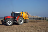 Red tractor with yellow sprayer tank — Stock Photo