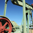 Detail of small scale crude oil pump udner sky — Stock Photo #33929773