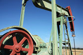 Detail of small scale crude oil pump udner sky — Stock Photo