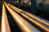 Long pipe line in oil refinery during sunset — Stock Photo