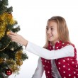 Girl decorates the Christmas tree — Stock Photo