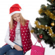 Girl with gifts near a Christmas tree — Stockfoto #37362721