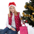 Stock fotografie: Girl with gifts near a Christmas tree