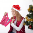 Girl with gifts near a Christmas tree — Stockfoto #37362791