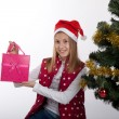 Foto de Stock  : Girl with gifts near a Christmas tree