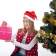 Girl with gifts near a Christmas tree — Stockfoto