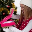 Girl with gifts near a Christmas tree — Stockfoto #37363745