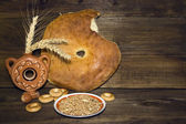 Round loaf of bread, bagels and wheat on a background of wooden — Stock Photo