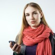 Young blonde girl with mobile phone in hand — Stock Photo