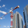 Stock Photo: Building crane on background of high-rise buildings