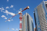 Building crane on a background of high-rise buildings — Stock Photo