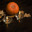 Pumpkin and two lighted candles on a dark background — Stock Photo