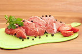 Piece of raw meat with spices and vegetables — Stock Photo
