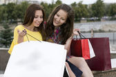 Smiling girls look in a package with purchase — Stock Photo