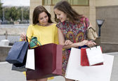 Young girls look in a package with purchase — Stock Photo