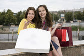 Smiling girls opened a package with purchase — Stock Photo
