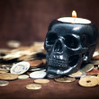 Stock Photo: Close up skull candleholder with coins