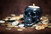 Close up skull candleholder with coins — Stock Photo