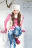 Smiling girl sitting on snow winter background — Stock Photo