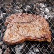 Rump steak cooking on a charcoal barbecue. — Stock Photo