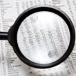 Magnifying glass over stocks and shares - Stock Photo