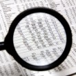 Magnifying glass over stocks and shares — Stock Photo