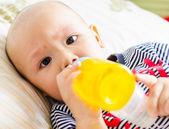 Baby trinkt orangensaft — Stockfoto