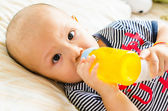 Baby drinking orange juice — Stockfoto