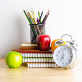 Note books, clock, pencils, apples on the table — Stock Photo