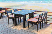 Table and chairs on the beach — ストック写真