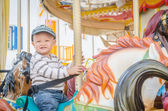 Child on the carousel horse — Stock Photo