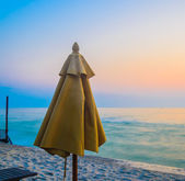 Umbrella on the beach in twilight — Stok fotoğraf
