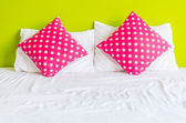 Colorful polka pillow on white bed — Stockfoto