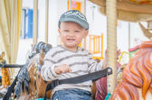 Children play carousel horse — Foto Stock