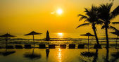 Silhouette pool beach and palm tree sunset times — ストック写真