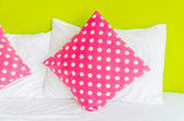 Colorful polka pillow on white bed — ストック写真