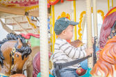 Children play carousel horse — Stock Photo