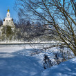 Church on the shore of frozen river — Stock Photo