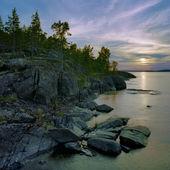 Sunset at stony shore of Ladoga lake, Russia — Stock Photo